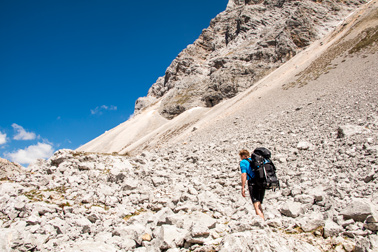 Man trekking on a gravel path in the Julian Alps
